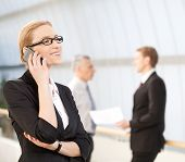 pic of people talking phone  - Cheerful mature woman in formalwear talking on the mobile phone and smiling while her colleagues talking on background - JPG