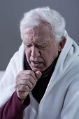 foto of cough  - Ill coughing senior man covered with blanket - JPG