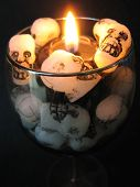 stock photo of magickal  - A black candle with wax skulls. ** Note: Slight blurriness, best at smaller sizes - JPG