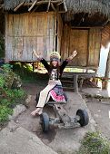 stock photo of hmong  - Traditionally dressed Mhong hill tribe woman at the wooden cottage - JPG