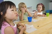 foto of daycare  - Children eat their snack during the break at the daycare - JPG