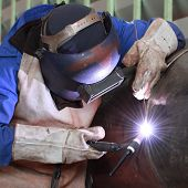 picture of welding  - Welder is welding big column with all the safety gear - JPG