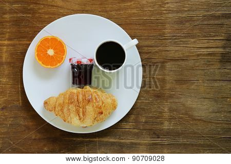 breakfast serving funny face on the plate (jam, croissant, orange and coffee)