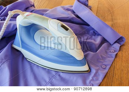 ironing shirt. Iron irons purple men's shirt.