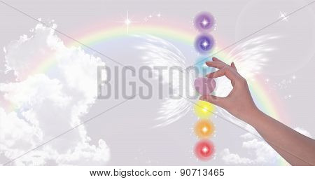 Hand Holding Rose Quartz Heart And The Seven Chakras