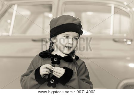 Cute Little Girl Dressed In Retro Coat Posing Near Oldtimer Car