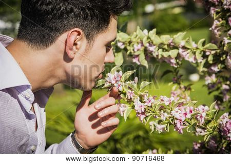 Young man in garden smelling beautiful flowers
