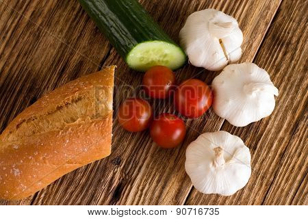 Four Tomatoes Among Garlic Cucumber And Baguette