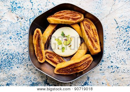 Indian savouries and milk sweet kept in a cup on a plain background