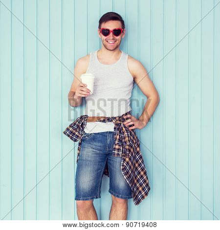 Portrait of funny smiling hipster man in red heart shaped glasses looking at camera holding paper cu