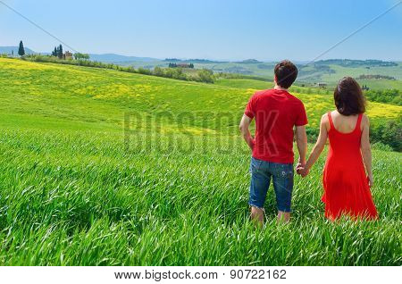 Romantic couple outdoors having fun and walking on green field, vacations in Tuscany, Italy