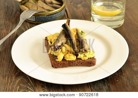 Sandwich with scrambled eggs and sprats