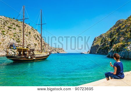 Young lady sitting in silent bay with port, Greece