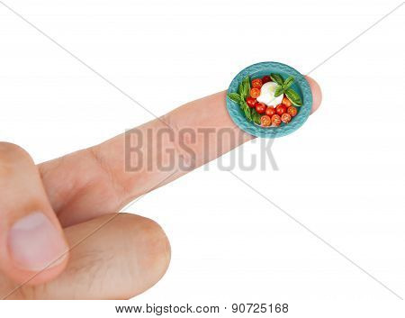 Dish With Mozzarella And Cherry Tomatoes In Miniature On Index Finger