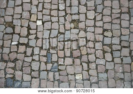 Pavement Of Grey And Pinkish Cobblestones As Background.