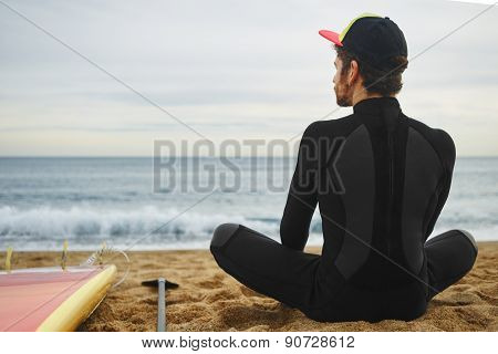 Portrait Of Handsome Young Surfer Man Sitting At Sand Near Ocean, Young Beautiful Surfer Man