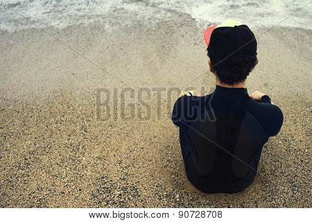 Handsome Young Surfer Man Sitting At Sand Near Ocean, Young Beautiful Surfer Man In Black Diving Sui