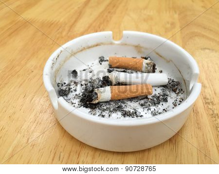 Burning Cigarette On Wood Table