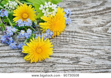 Dandelion And Forget-me On A Wooden Background