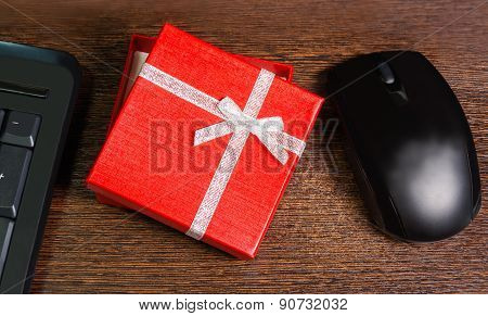 Composition With Red Gift Box,  Mouse And Keyboard Laying On Wooden Desk