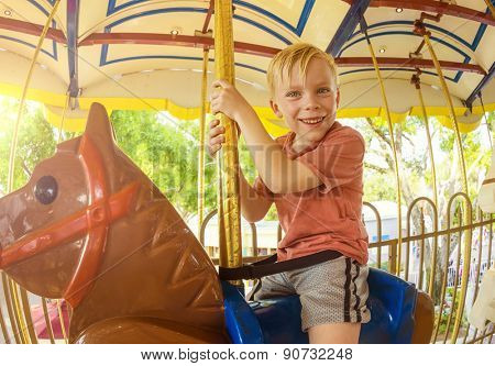 Cute little smiling boy riding on a Carnival Carousel at an amusement park or theme park. Warm afternoon sun in the background