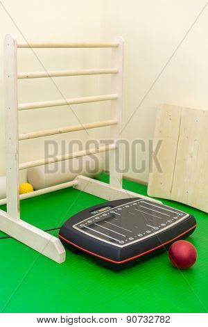 vibroplatform and ball on green mat in physiotherapist office