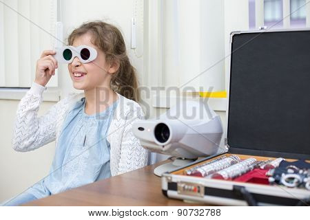 girl in red and green glasses at ophthalmologist