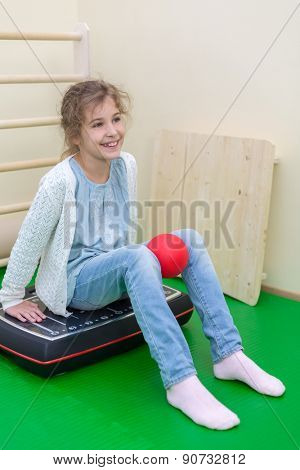 girl squeezes the ball knees seating on vibroplatform