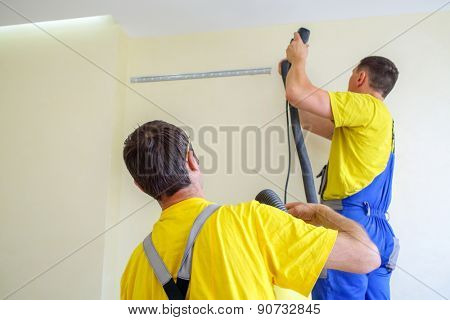two male furniture assemblers in uniform drill walls with a vacuum cleaner