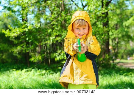 smiling boy stands on lawn in  summer park