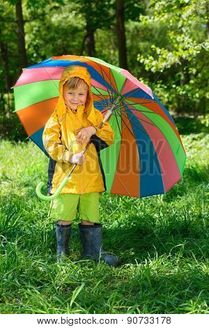 smiling boy with colorful umbrella stands on lawn in  summer park