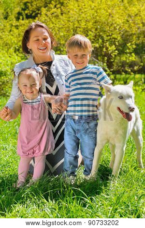 Mom with her daughter and son sitting with dog on grass in park