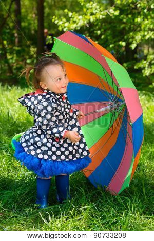 smiling girl with colorful umbrell�?��?�° stands on lawn in summer park