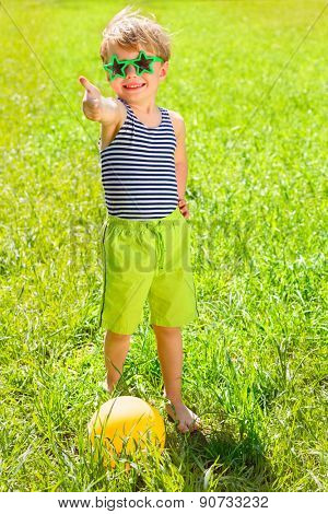 boy in park in striped t-shirt and sunglasses raised his thumb up, ball are in grass