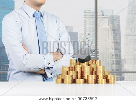 Student Is Crossed His Hands In Front Of The Graduation Hat And Coins Pyramid. A Concept Of A High P