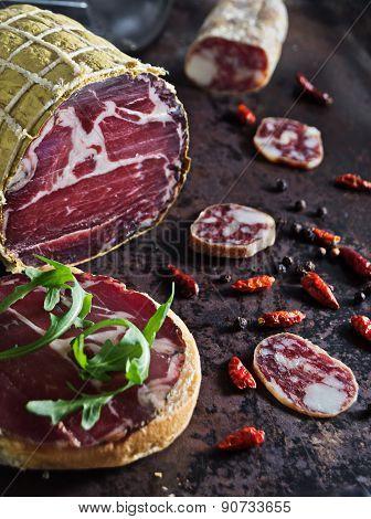 Cured Pork Shoulder With Salami Over Black Metal Surface.