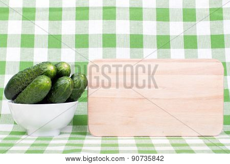 Cucumbers In A White Bowl On A Checkered Napkin Beside Cutting Board And Place For Text, Side View