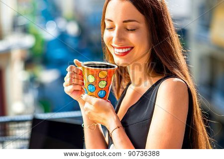 Woman with colorful coffee cup on the balcony
