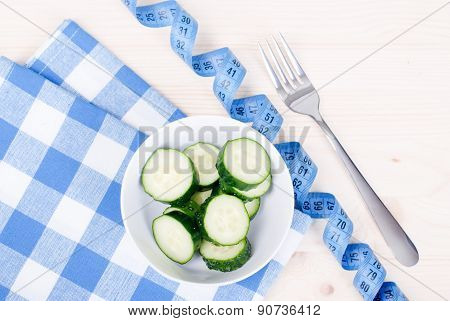 Cucumber Salad On A Checkered Napkin Beside Centimeter And Fork, Top View