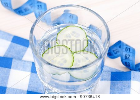 Glass Of Water With Slices Of Fresh Cucumber On A Checkered Napkin Beside Centimeter, Side View