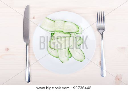 Thinly Sliced Cucumber In A Plate, Fork And Knife Next To The Light Table, Top View