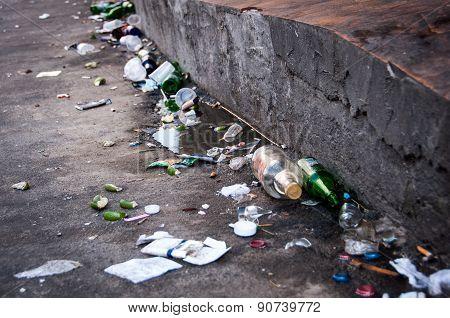 Trash in the street, empy beer bottles