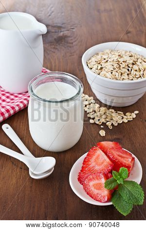 Yogurt In A Glass Jars With Strawberry And Oatmeal On Dark Wooden Background.