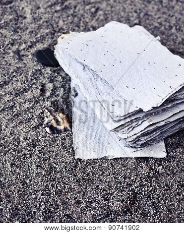 Beach background with copy space, beach sand summer theme, stack of blank papers over sand texture,