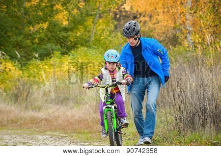 Father teaching child to ride bike in autumn park, family sport