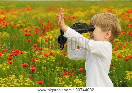 Boy in a field with binoculars