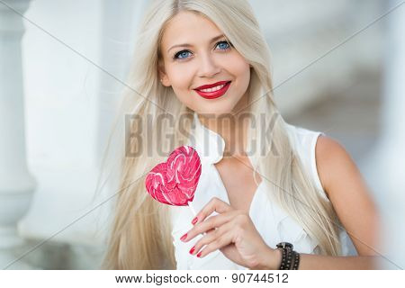 Portrait beautiful young sexy blond girl with red lollipop heart.