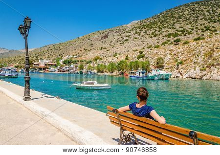 Young lady in blue sitting on bench, Greece