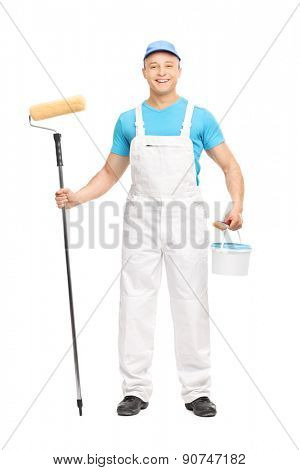 Full length portrait of a male house painter holding a paint roller, a brush and a color bucket isolated on white background