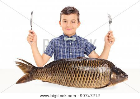 Little kid holding a fork and a knife seated at a table with a huge raw fish in front of him isolated on white background